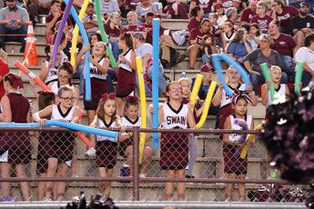 Fans at Swain football game including cheerleaders and fans with pool noodles