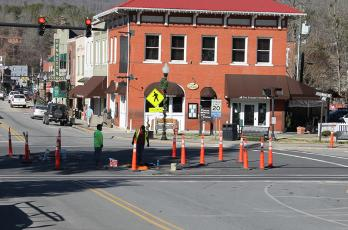 Contractors with Teraflex continue work on the water and sewer lines on Main Street with one man emerging from the manhole on the street.