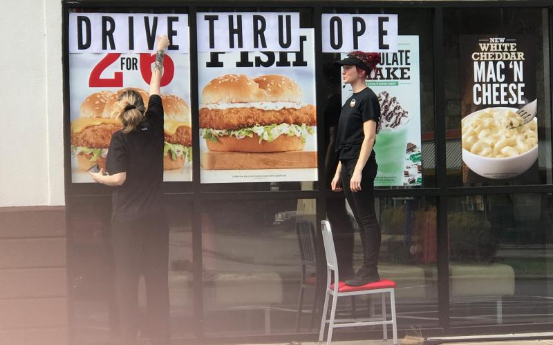 "Employees at Arby's post a sign on the window that reads ""Drive Thru Open"" following Gov. Roy Cooper's order last week that restaurants can no longer have dine-in service. It's one of many measures the government has put in place to try to stop the spread of coronavirus."